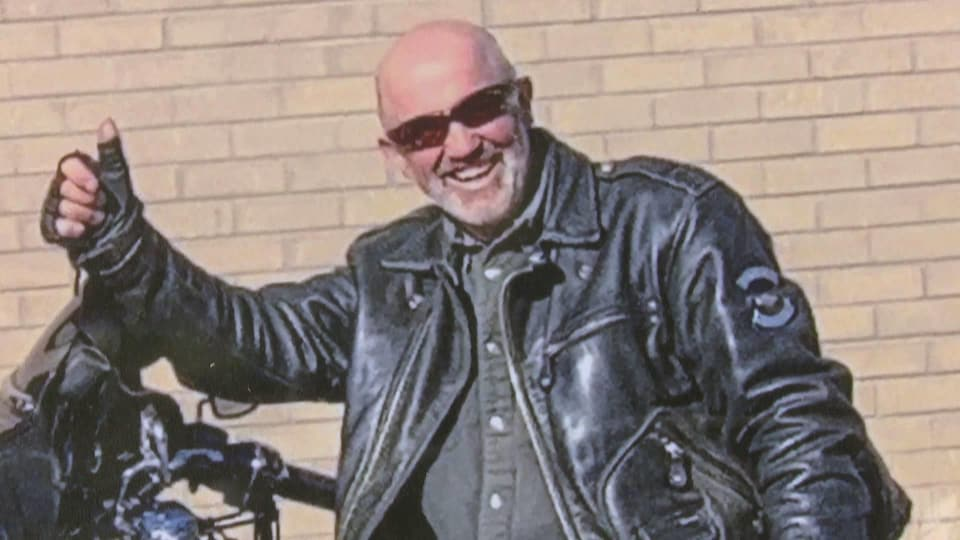 Un homme lève le pouce droit et sourit. Il est vêtu d'un blouson de cuir et pose à côté de sa moto.