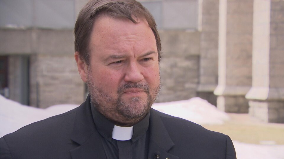 Un homme donne une entrevue devant une église.