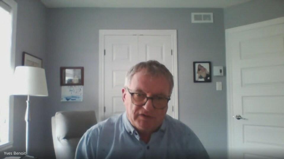 Un homme portant une chemise bleue devant son ordinateur.