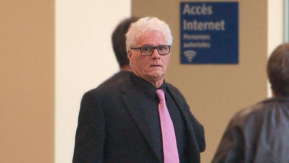 Yves « Colosse » Plamondon, un homme aux cheveux blancs, regarde la caméra. Il porte une cravate rose et un complet noir.