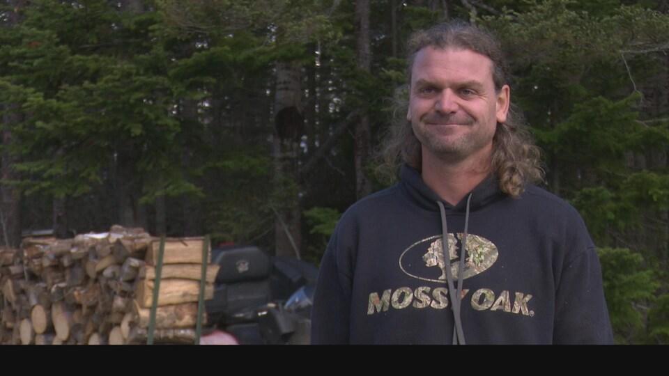 Un homme dehors près d'une corde de bois