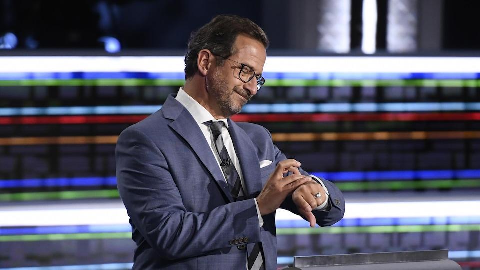 Yves-François Blanchet regarde sa montre en souriant.