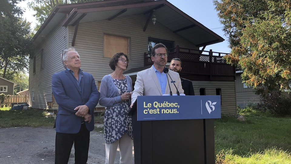 Yves-François Blanchet fait une annonce devant une maison endommagée par un sinistre.