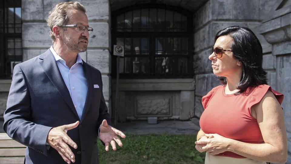 Yves-François Blanchet discute avec Valérie Plante devant l'édifice.