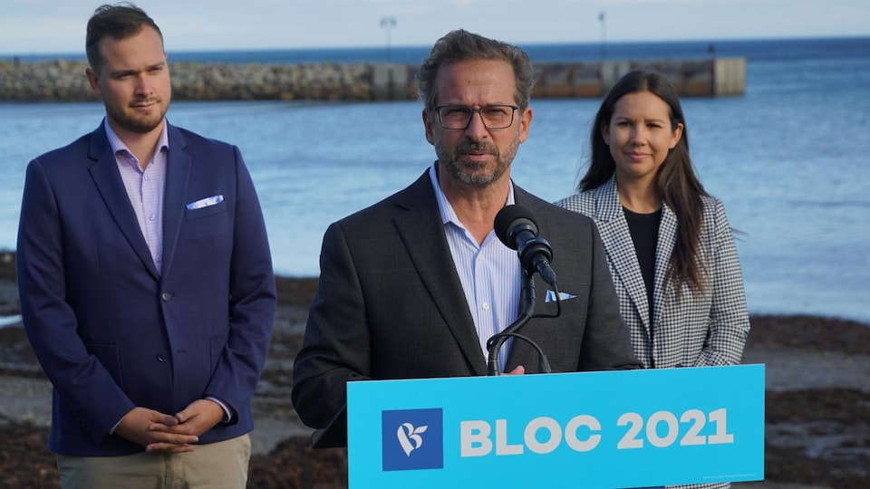 Le chef du Bloc québécois Yves-François Blanchet, photographié derrière un lutrin et devant les deux candidats Maxime Blanchette-Joncas et Kristina Michaud.