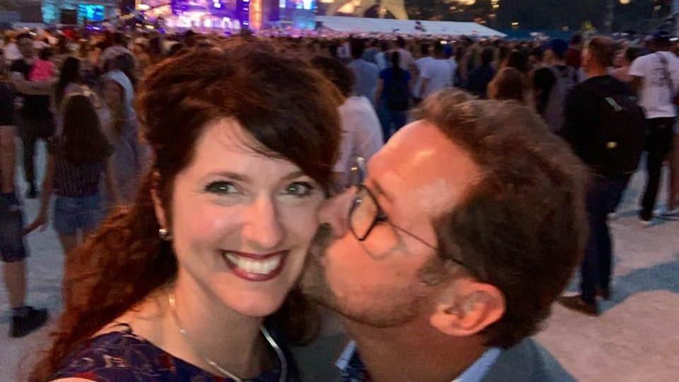 Un homme embrasse sur la joue une femme. Elle sourit.