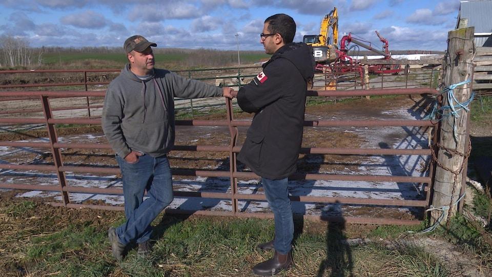 Le producteur discute avec un journaliste de Radio-Canada sur sa ferme laitière.