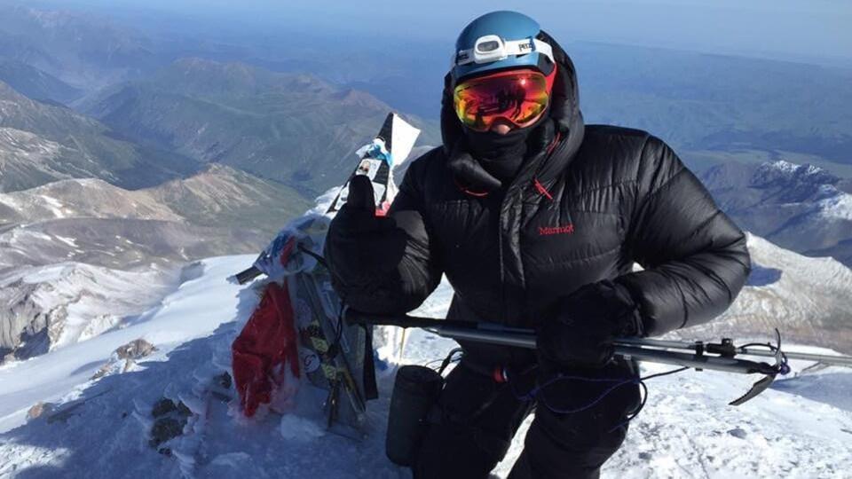 Un homme habillé chaudement sur une montagne enneigée.