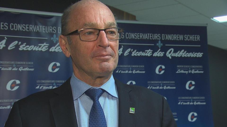 Le maire Yves Lévesque devant les panneaux de la tournée québécoise de consultation d'Andrew Scheer