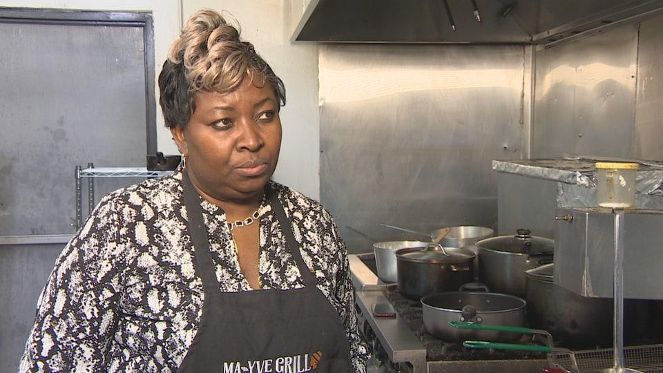 Yvette Kavungu dans sa cuisine avec un tablier au cou.