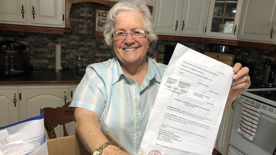 Une femme souriante avec lunettes et cheveux blancs montre une feuille de papier dans sa cuisine.
