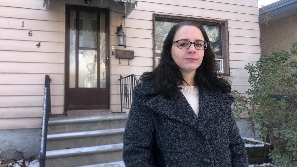 Yvette Mathieu est devant chez elle dehors avec un manteau.
