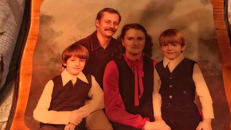 Une vieille photo de famille qui comprend quatre personnes.