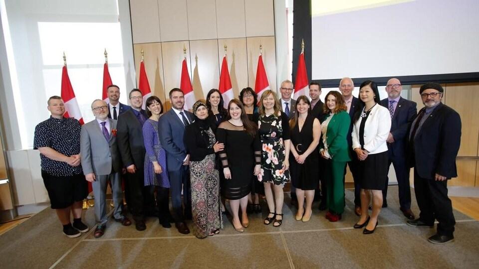 Un groupe de personnes devant des drapeaux canadiens.