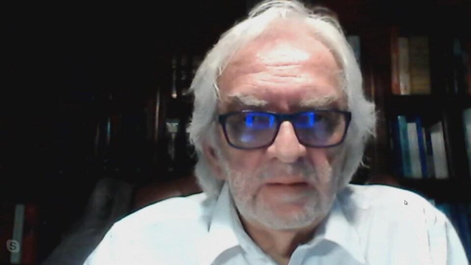 Un homme aux cheveux blancs et portant des lunettes en entrevue devant son écran d'ordinateur.