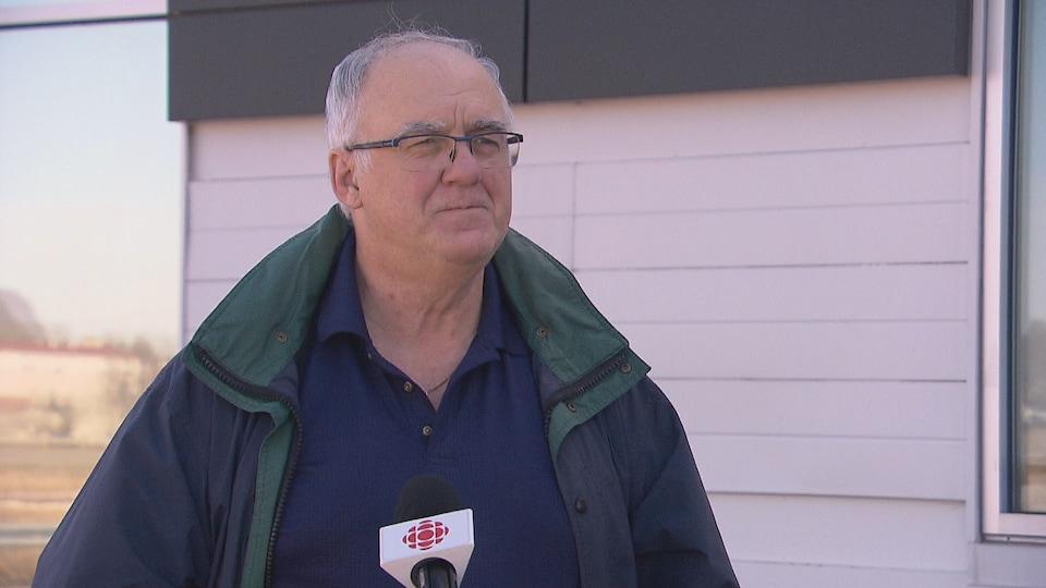 Un homme portant un manteau lors d'une entrevue.