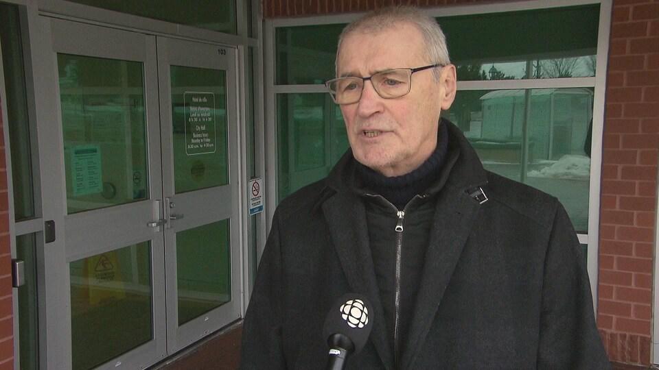 Yvon Lapierre devant un micro de Radio-Canada, à l'extérieur devant un bâtiment.