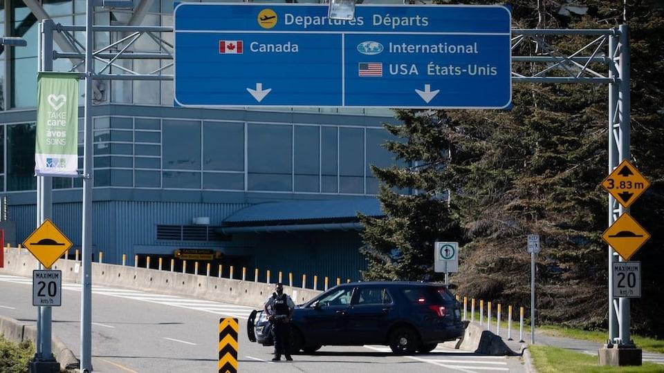 Un policier bloque la route à l'aéroport international de Vancouver.