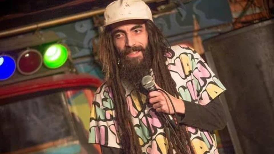 L'homme barbu porte une casquette et tient un micro.