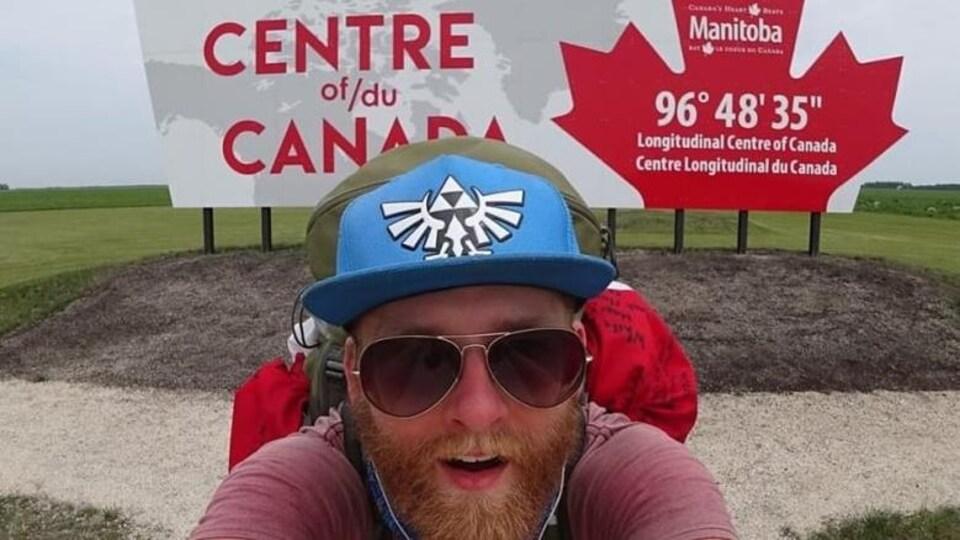 Autoportrait de Zayell Johnston avec en arrière-plan un panneau affichant «Centre du Canada, Manitoba».