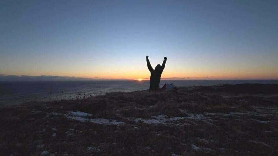Plan large sur Cape Spear à l'aube, Zayell Johnston, à genou, lève les bras en l'air pour exprimer sa joie.