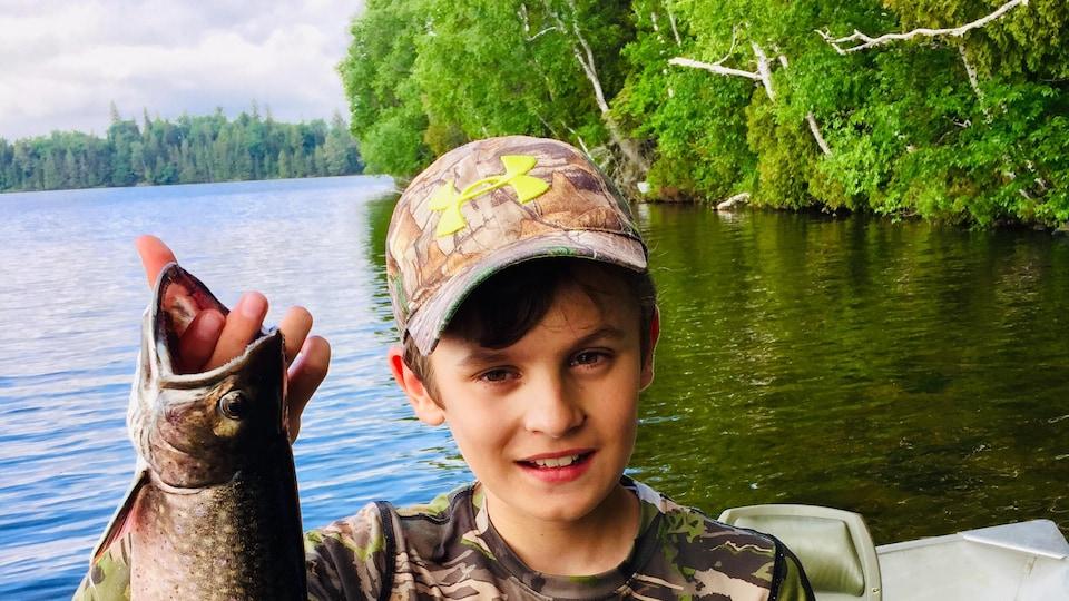 Un enfant tient une truite arc-en-ciel qu'il vient de pêcher.