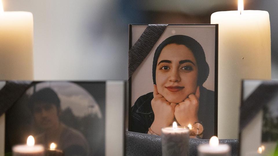 Une photo de Zeynab Asadi Lari est visible entre deux chandelles.