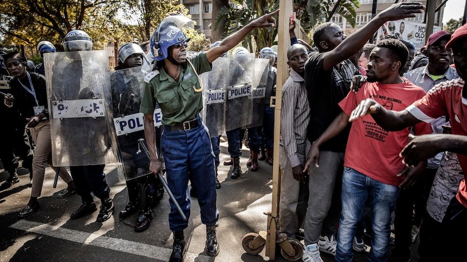 Des nombreux policiers antiémeutes sont rangés près d'une barricade, derrière laquelle se trouvent des partisans de l'opposition.