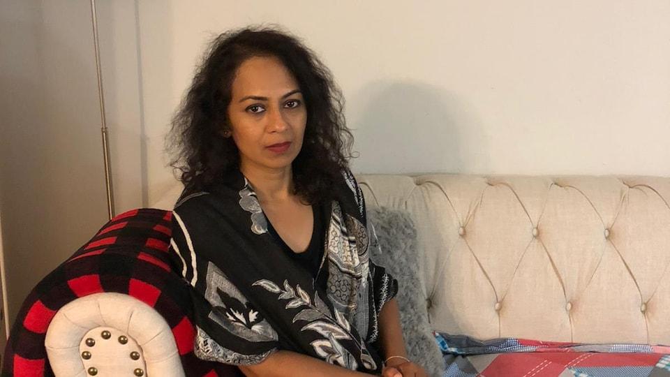 Une femme assise dans son salon.