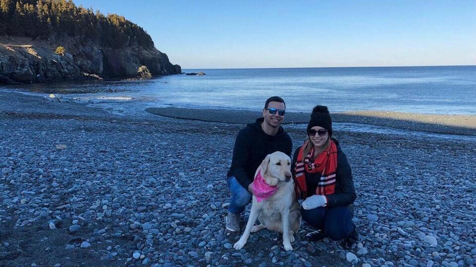 Un couple et un chien sur le bord de l'eau.