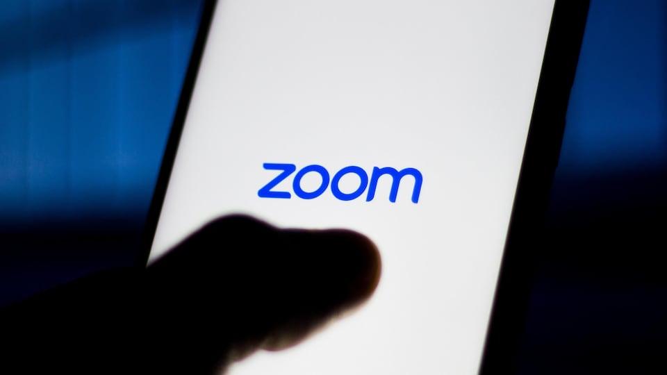 Une personne tient un téléphone intelligent qui affiche le logo de l'application Zoom.