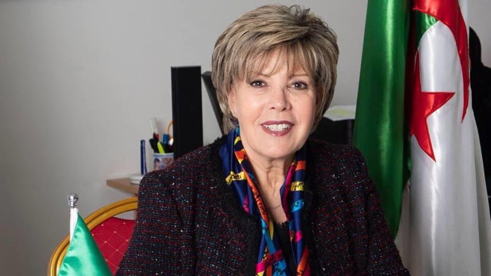 Elle est assise devant un drapeau algérien et sourit.