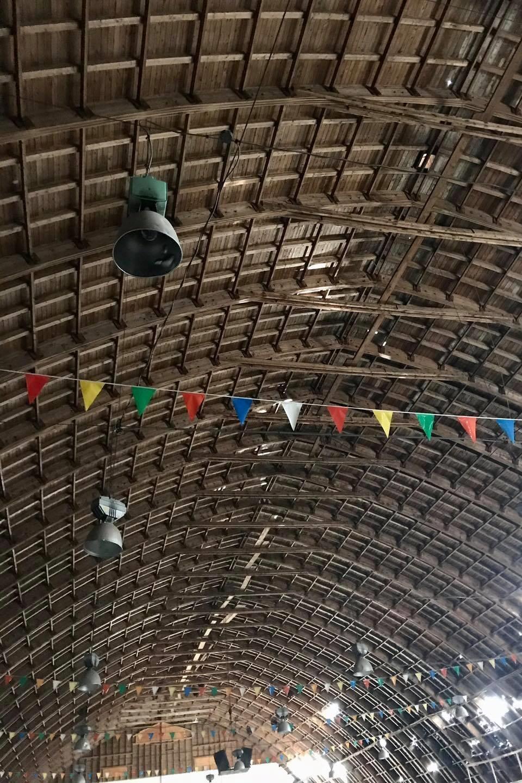 Un plafond en arches de bois recouverts de planches, vu de l'intérieur de l'aréna.