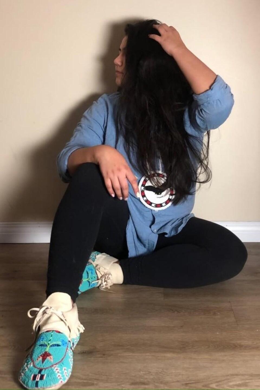 Ashley Daniels est assise et montre fièrement ses mocassins de couleur turquoise.