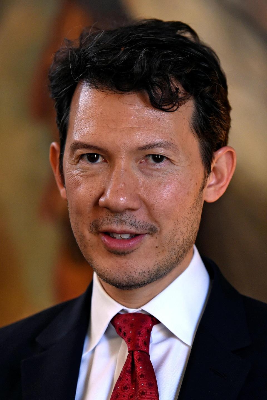 Un homme en veston-cravate regarde droit devant lui en souriant.