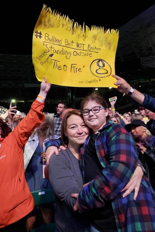 Des gens tiennent bien haut la pancarte de Camille, pendant que Mme Baragar tient sa fille dans ses bras.
