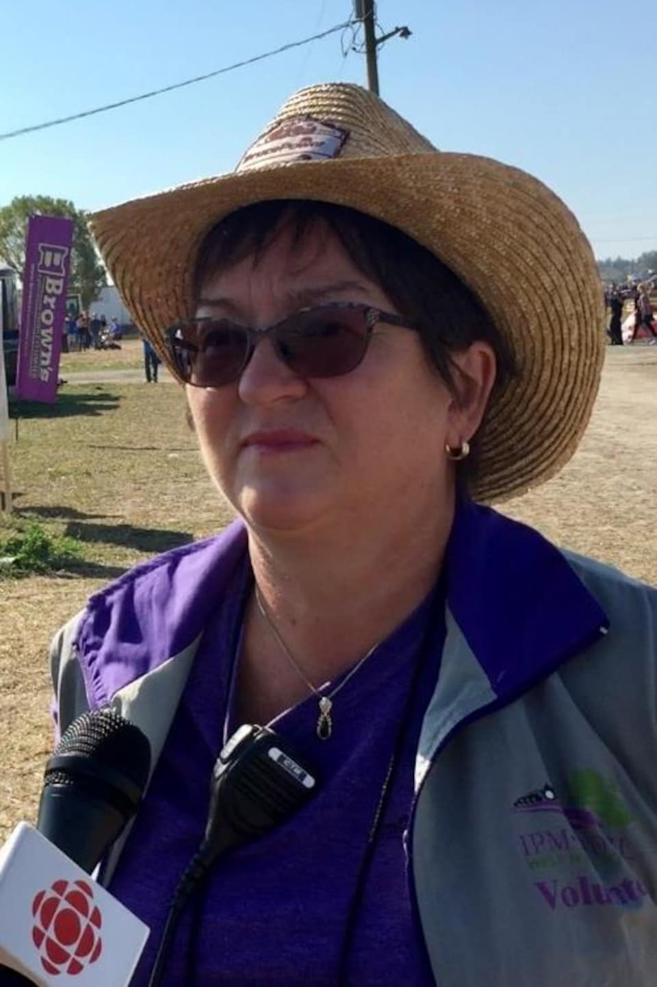 Une femme avec un chapeau sous le soleil dans un festival.