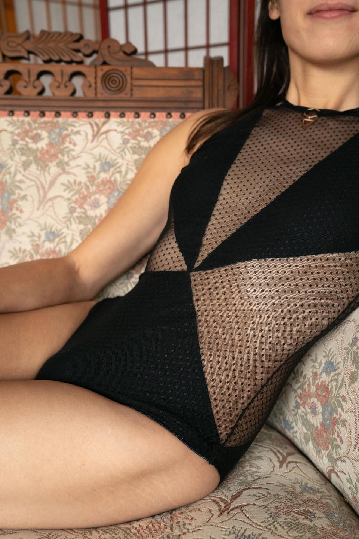Abigail est assise sur un divan et porte un morceau de lingerie noir, qui laisse entrevoir les côtés de son corps et le haut de son poitrail.