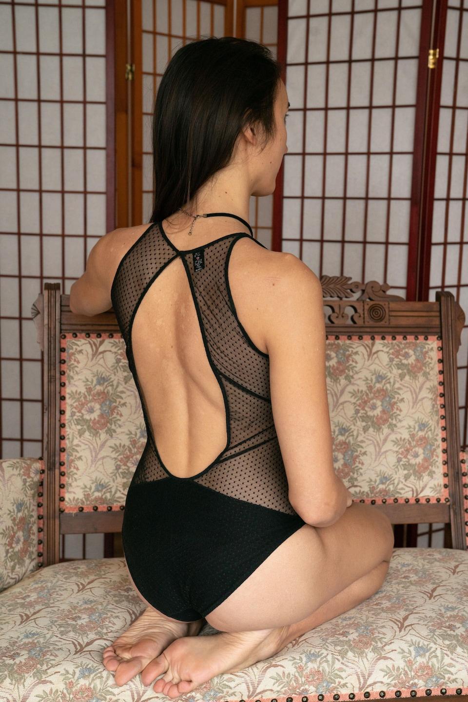 Abigail est agenouillée sur le divan et expose son dos à la caméra.