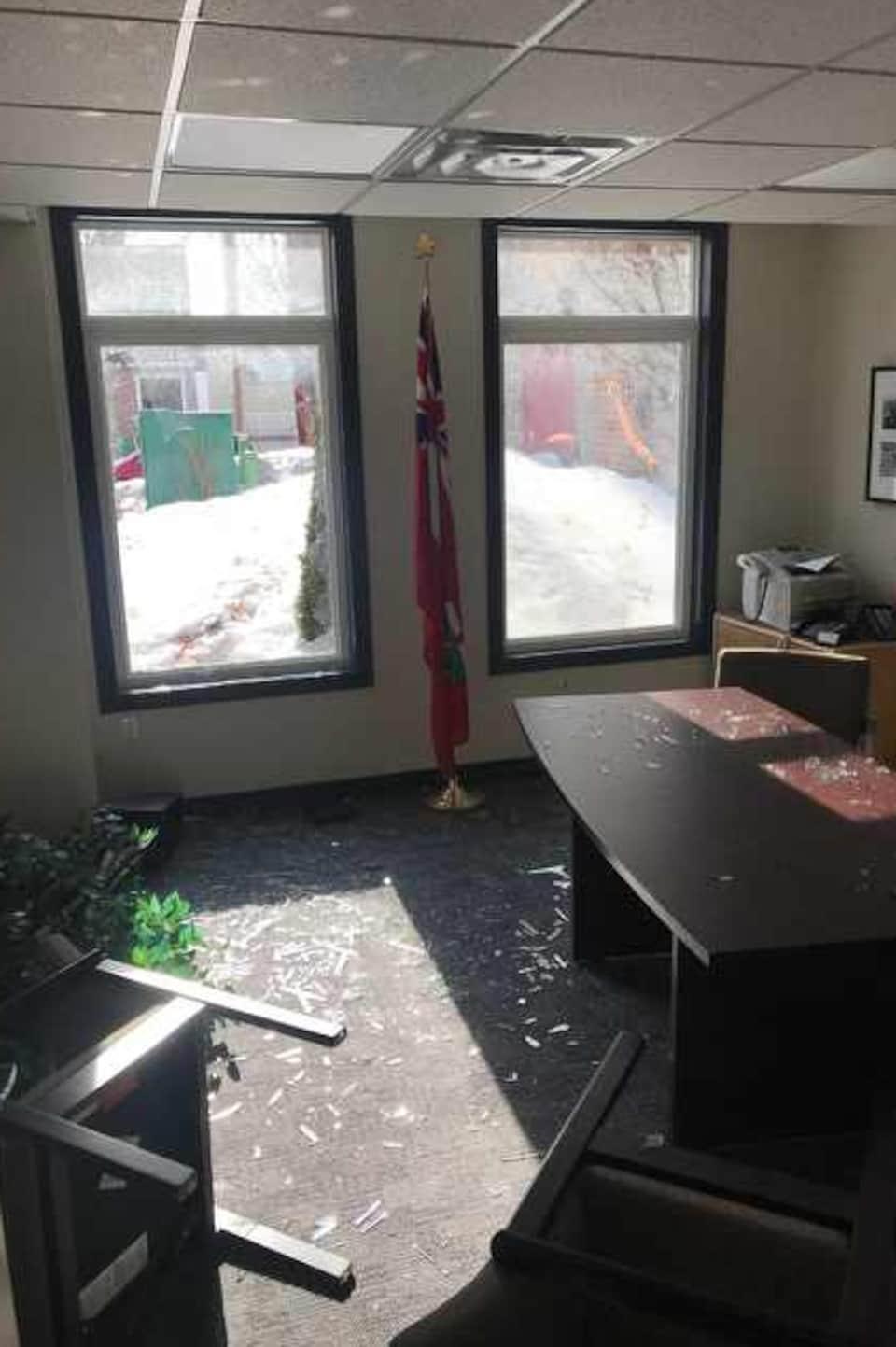 Photo de la fenêtre fracassée d'un bureau; des chaises sont renversées sur le plancher où il y a aussi des débris.