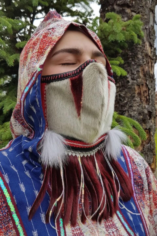 Une femme arbore un masque artistique.