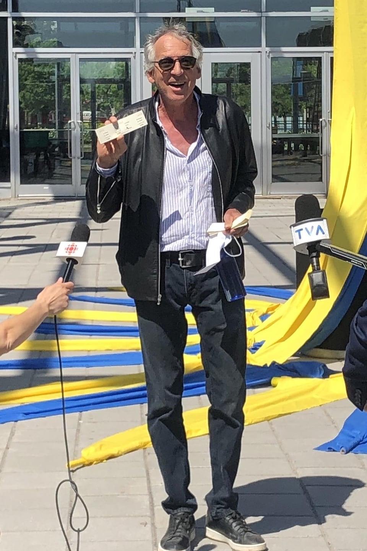 Gilles Sainte-Croix montre un billet à des journalistes.