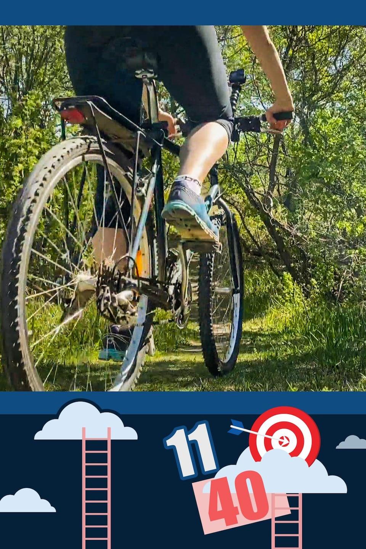 Une femme roule dans un sentier en forêt à l'aide d'un vélo de montagne.