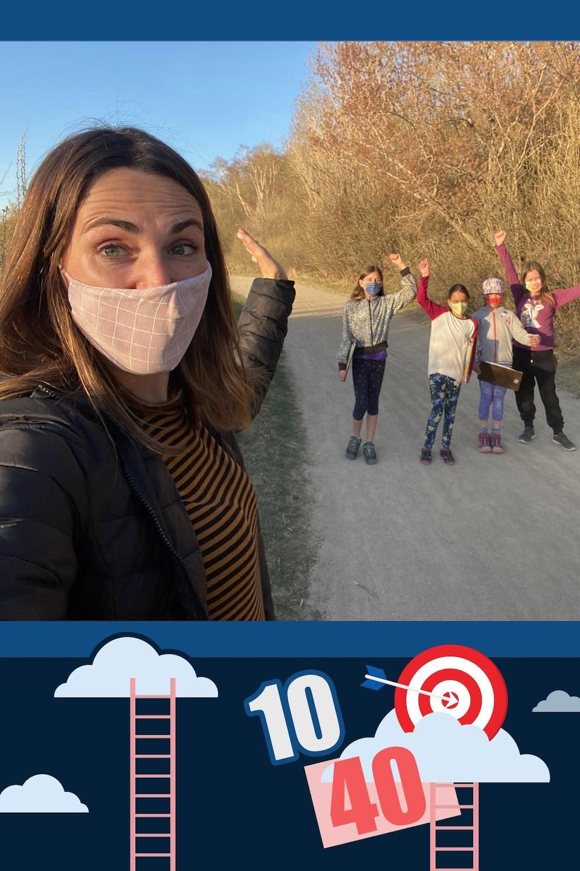 Nicole et des enfants posent pour une photo, les bras levés vers le ciel, le long d'un sentier près de la rivière.