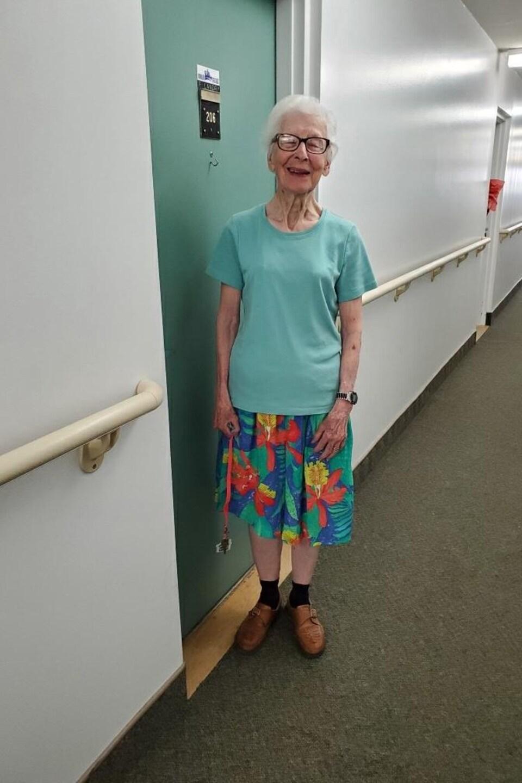 Une femme devant sa chambre.