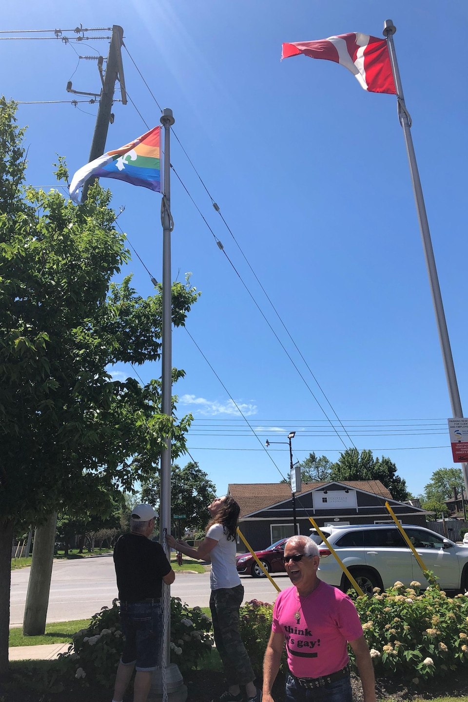 Trois personnes souriantes s'assurent que le drapeau est bien dans les airs.