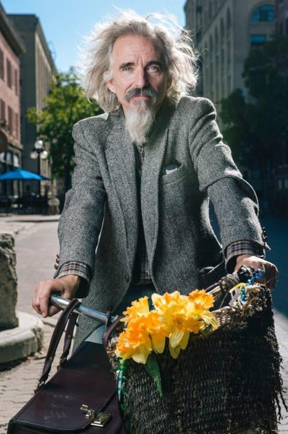 Un homme avec une barbichette sur un vélo avec des fleurs.