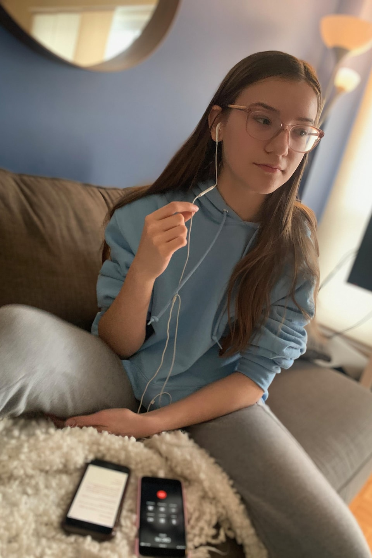 Émilie Vermette assise sur un canapé porte des écouteurs pour téléphoner depuis son cellulaire.