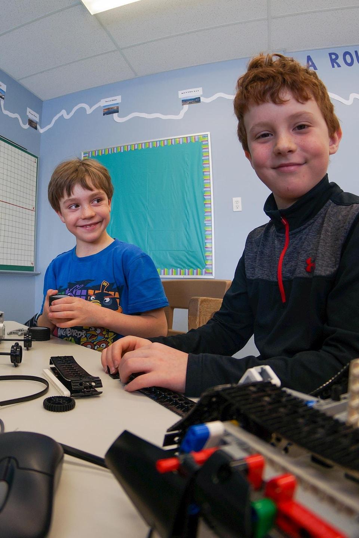 Deux jeunes garçons fabriquent un robot.