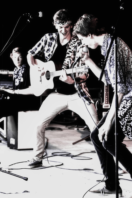 Un jeune homme, guitare en main, joue avec deux autres personnes.